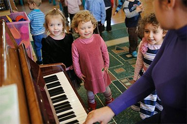 Instructor plays piano for kids